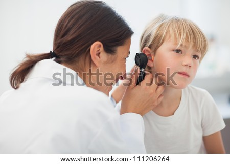 Doctor auscultating the ear of a child in examination room - stock photo