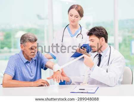 Doctor bandaged hand to his mature patient at hospital. - stock photo