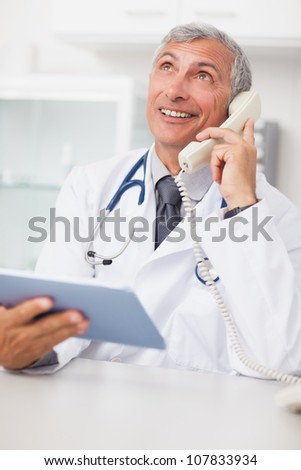 Doctor calling while holding a tablet computer in medical office - stock photo