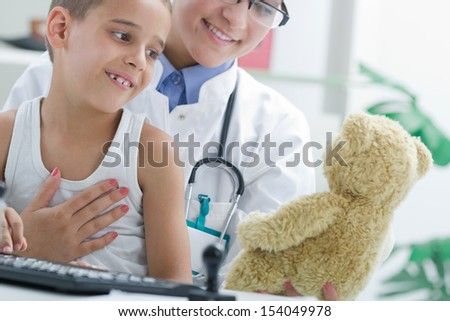 Doctor calms a young boy, playing with teddy bear - stock photo