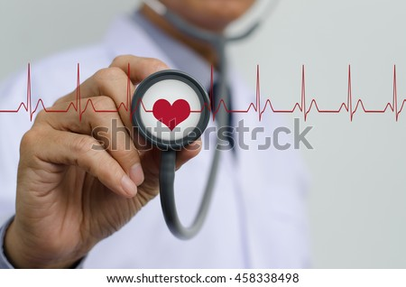 Doctor (cardiologist) with stethoscope in hand and EKG (electrocardiogram) graph monitor, health and medical concept. - stock photo