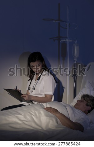 Doctor caring about terminally ill patient at night - stock photo
