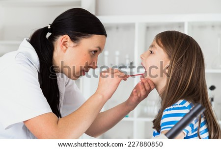 Doctor check throat of little girl - stock photo