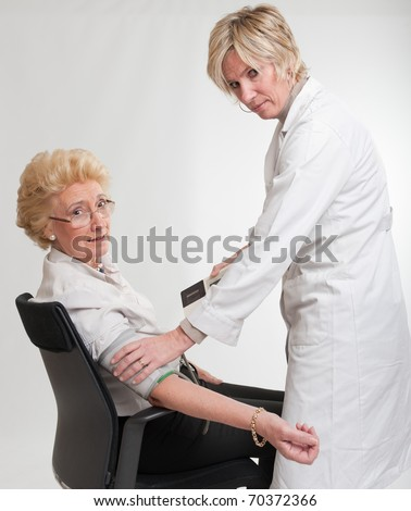 Doctor checking a lady?s blood pressure - stock photo