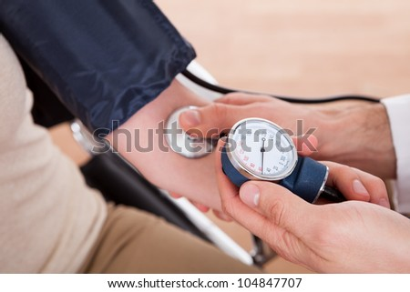 Doctor checking blood pressure of a woman. Close-up shot