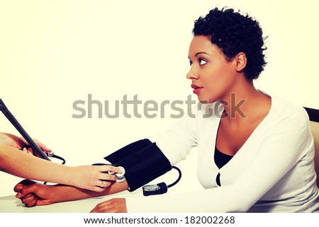 Doctor checking blood pressure of pregnant woman - stock photo