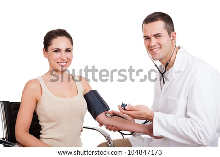 Doctor checking blood pressure of young woman. Isolated on white