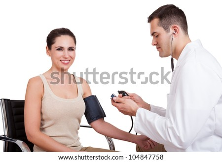 Doctor checking blood pressure of young woman. Isolated on white - stock photo