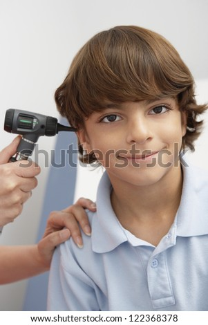 Doctor checking boy's ear with otoscope in clinic - stock photo