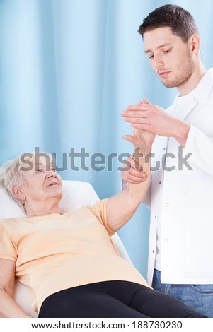 Doctor checking elderly female patient's injured arm