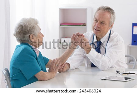 Doctor checking elderly female patient's injured arm - stock photo