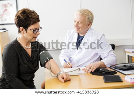 Doctor Checking Female Patient's Blood Pressure - stock photo