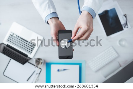 Doctor checking heartbeat on mobile phone using a stethoscope, desktop with medical equipment on background, medical app concept - stock photo