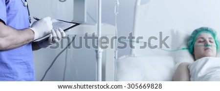 Doctor checking lab test results of his patient  - stock photo