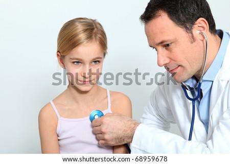 Doctor  checking little girl breathing - stock photo