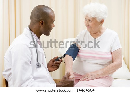 Doctor checking woman's blood pressure in exam room smiling - stock photo