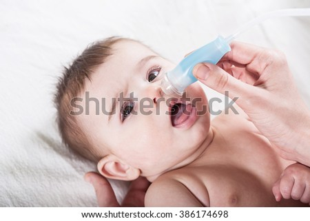 Doctor cleans the nose of little baby. Health care and medicine concept at pediatrician department.