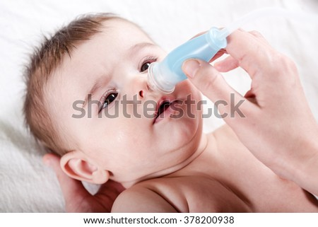 Doctor cleans the nose of little baby. Healthcare and medicine concept at pediatrician department.