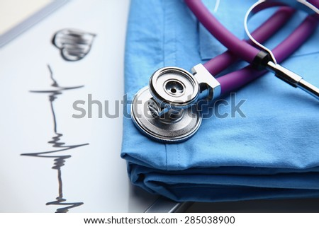 Doctor coat with stethoscope on the desk .