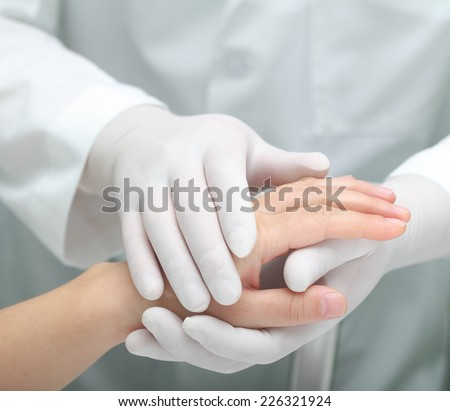 Doctor comforting a sick woman. Hands in warm touch. - stock photo