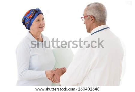 Doctor comforting woman suffering from cancer - stock photo