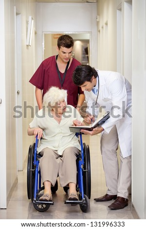 Doctor communicating with disabled senior female patient in hospital corridor
