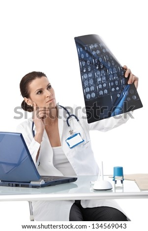 Doctor concentrating on studying x-ray scan at office desk, isolated on white.