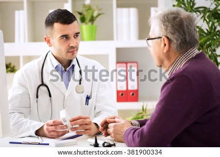 Doctor consulting old patient with medicine drugs - stock photo