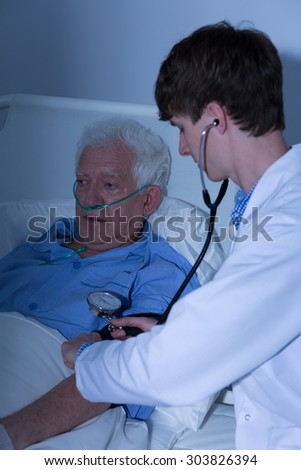 Doctor controlling blood pressure of elder man - stock photo
