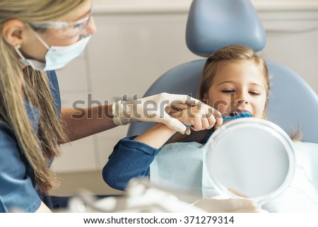 Doctor dentist teaching a child to brush teeth. Dentist Concept. - stock photo