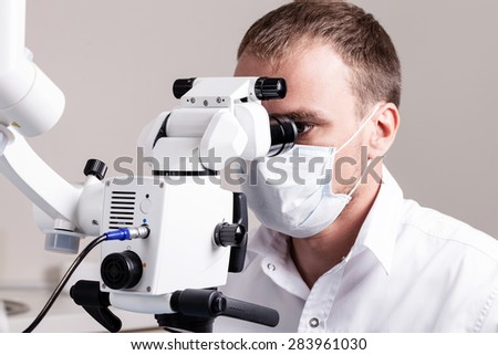 Doctor dentist using dental microscope in modern dental office for operation of a woman patient -Dentistry - stock photo