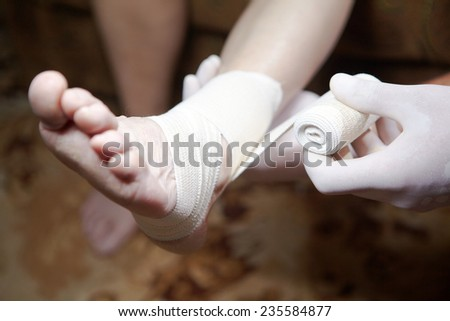 Doctor doing a bandage for patient. First aid
