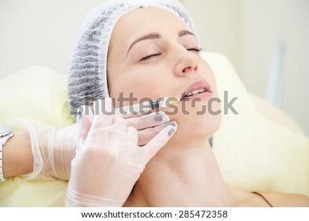 doctor doing cosmetic injection for young woman