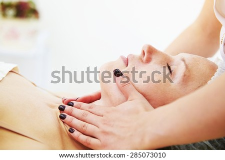 doctor doing facial massage for beautiful young woman at beauty studio - stock photo