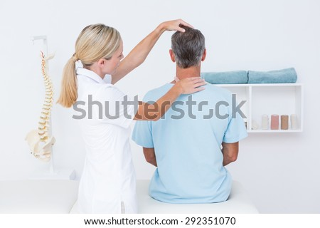 Doctor doing neck adjustment in medical office - stock photo