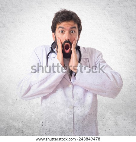Doctor doing surprise gesture over textured background - stock photo