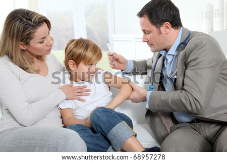 Doctor doing vaccine injection to little boy - stock photo