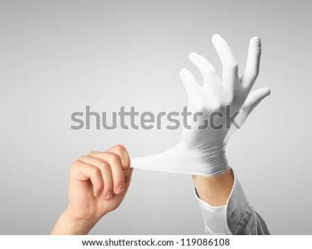 Doctor dress gloves on hands on gray background - stock photo