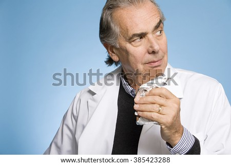 Doctor eating chocolate - stock photo
