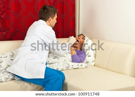 Doctor examine patient woman for sore throat in her  couch home - stock photo