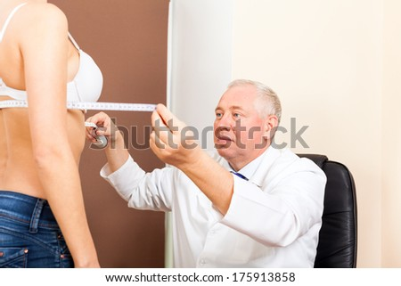 doctor examine woman breast measure with tape, plastic surgery - stock photo