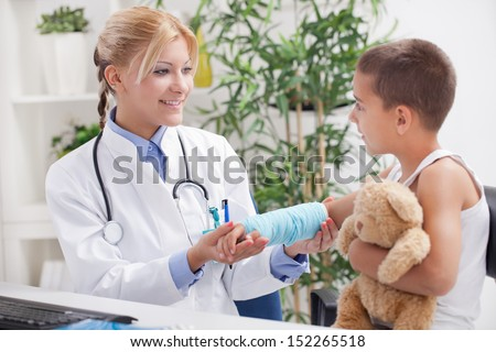 doctor examines an injured hand a little boy in office - stock photo