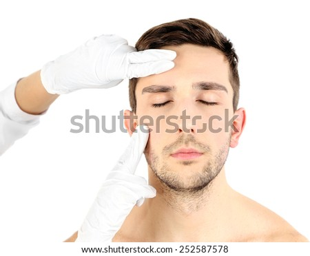 Doctor examines young man isolated on white - stock photo