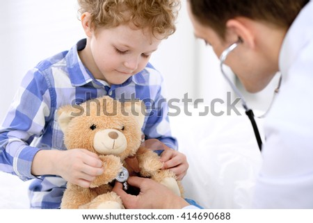 Doctor examining a child  patient by stethoscope - stock photo