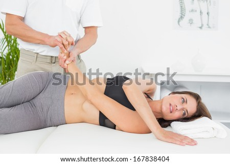 Doctor examining a female patient's hand in the medical office