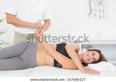 Doctor examining a smiling female patient's hand in the medical office