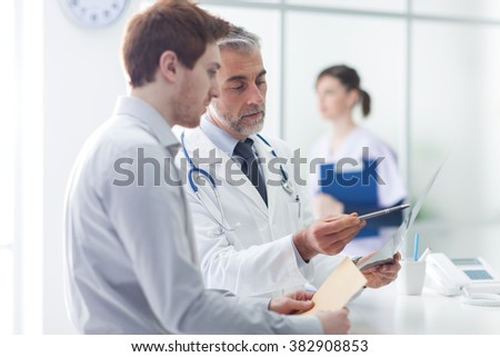 Doctor examining an x-ray and pointing, the patient is listening and watching, healthcare concept