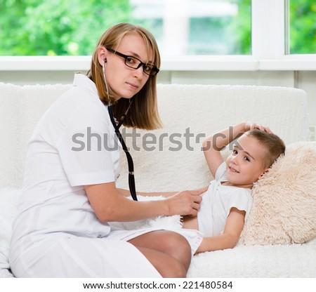 doctor examining boy with stethoscope - stock photo