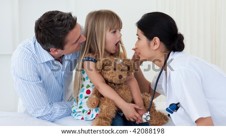 Doctor examining child's throat during a check-up - stock photo