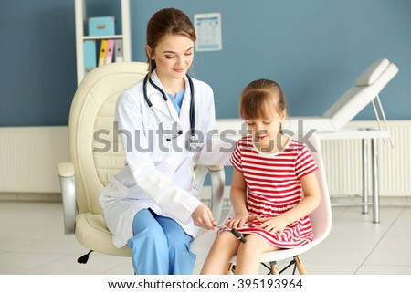 Doctor examining girl with a reflex hammer in the office